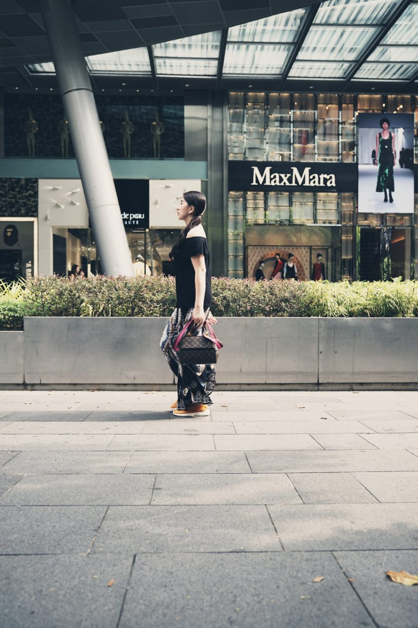 woman carrying bag in front of MaxMara building